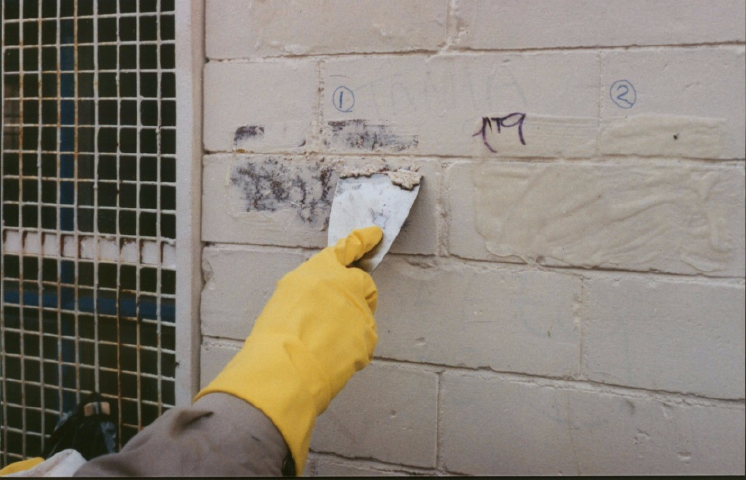 Masonry paint, softened by Safer* Paint & Varnish Remover being removed with a scrapper